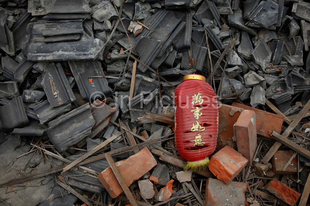 """A broken red lantern with the characters """" wan shi ru yi"""", or """"ten thousand things accroding to your will"""", sits on the rubble of a demolished house house that is slated for redevelopment in Shanghai China, on  May 01, 2011. The government has installed a series of measures in hope of curbing housing prices in major cities, which has sky rocketed in recent years out of the reach of ordinary families. While the effectiveness of these measures remain to be seen, as one of the main cause is the high cost of land, which is owned by the government, the restrictions has caused a real estate boom in smaller cities that are quickly becoming a problem of its own."""