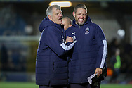 AFC Wimbledon manager Glyn Hodges shaking hands with AFC Wimbledon goalkeeping coach Ashley Bayes and smiling and laughing during the EFL Sky Bet League 1 match between AFC Wimbledon and Doncaster Rovers at the Cherry Red Records Stadium, Kingston, England on 14 December 2019.