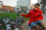 Feral pigeon (Columba livia), Manchester, UK. Young woman feeding pigeons in Manchester City Centre. Model released.
