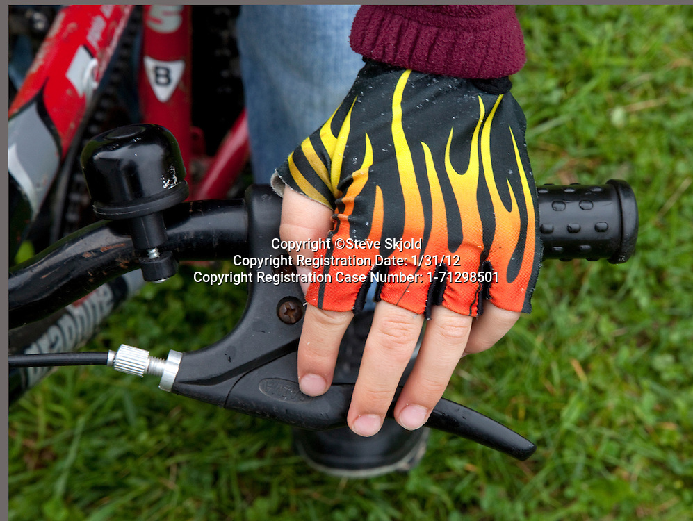 Polish boy age 8 wearing cool blazing hot fingerless gloves ready to ride his bicycle. Zawady Central Poland