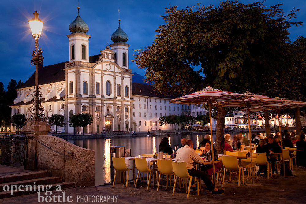 The Jesuit Church at dusk, with diners dining al fresco in the foreground, Lucerne, Switzerland.