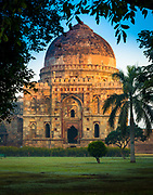 "Lodi Gardens is a park in Delhi, India. Spread over 90 acres, it contains, Mohammed Shah's Tomb, Sikander Lodi's Tomb, Sheesh Gumbad and Bara Gumbad, architectural works of the 15th century Sayyid and Lodhis, an Afghan dynasty, that ruled parts of northern India and Punjab and Khyber Pakhtunkhwa province of modern day Pakistan, from 1451 to 1526. The site is now protected by the Archeological Survey of India (ASI). The gardens are situated between Khan Market and Safdarjung's Tomb on Lodhi Road and is a hotspot for morning walks for the Delhiites.<br /> .....<br /> In the middle of the gardens is the Bara Gumbad (""Big Dome""), it consists of a large rubble-construct dome, it is not a tomb[citation needed] but a gateway to an attached a three domed masjid (mosque), both built in 1494 during the reign of Sikander Lodi, there is also a residence surrounding a central courtyard, where the remains of a water tank can be seen. Opposite the Bara Gumbad is the Sheesh Gumbad (""Glass dome"") for the glazed tiles used in its construction, which contains the remains of an unknown family, this was also built during the reign of Sikander Lodi."