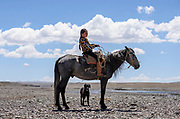 A Kyrgyz girl sits on her horse along a river in the At Bashi region, Naryn Province, Kyrgyzstan