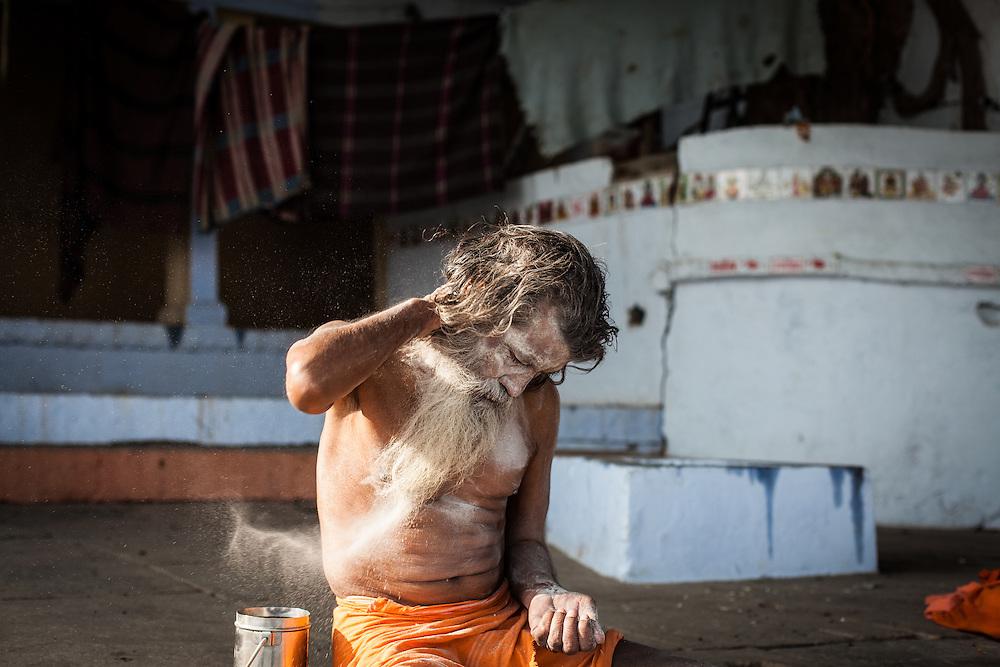 An Aghori Sadu himself his face with human ash.