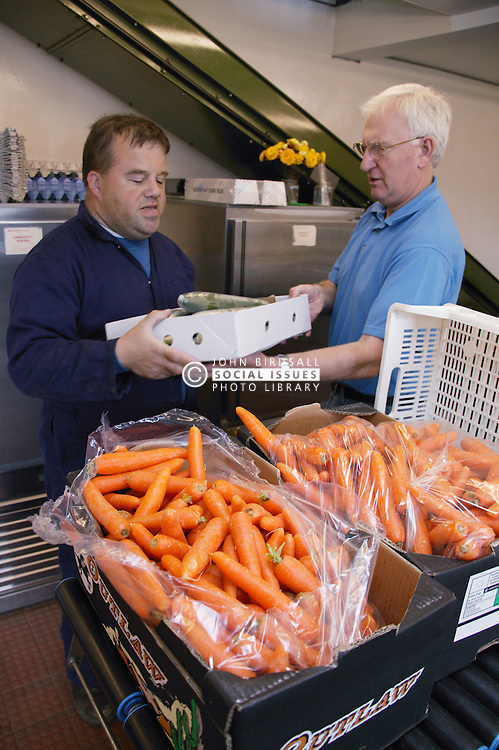 Man with learning disability at work at Brook Farm; Linby; carrying boxes of fresh vegetables,