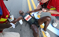 July 4, 2018 - Atlanta, GA, USA - Bernard Kip Lagat collapses to the ground after crossing the finish line to win the AJC Peachtree Road Race with a time of 28:45 in the 10K race on Wednesday, July 4, 2018, in Atlanta. (Credit Image: © Curtis Compton/TNS via ZUMA Wire)