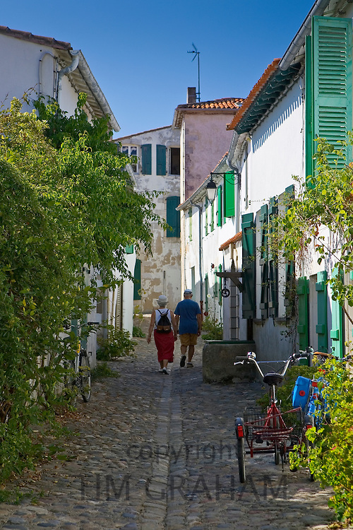 A couple walking down a cobbled street, St Martin, France.