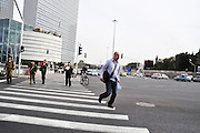 Israel, Tel Aviv, Azrieli tower highrise. Pedestrians cross the street