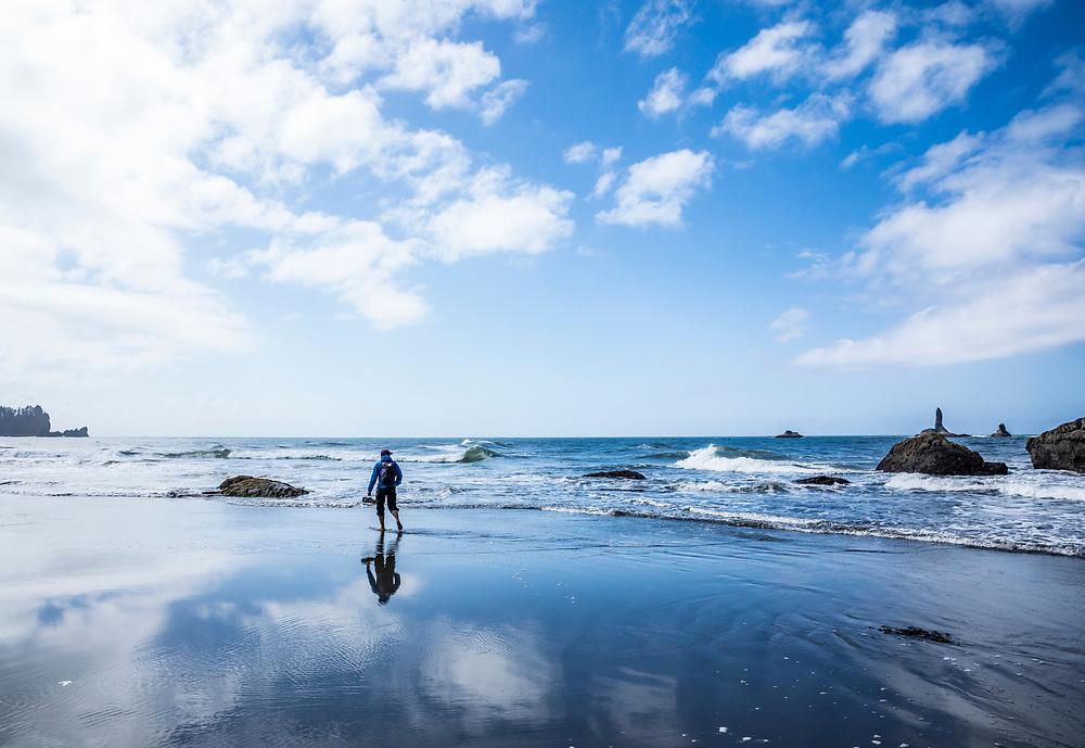 A woman walking bare foot on the beach. 2nd beach, Olympic National Park, Washington, USA.