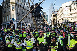 Environmental activists from Extinction Rebellion use three tripods to block a junction outside Mansion House underground station following a Blood Money March through the City of London on 27th August 2021 in London, United Kingdom. Extinction Rebellion were intending to highlight financial institutions funding fossil fuel projects, especially in the Global South, as well as law firms and institutions which facilitate them, whilst calling on the UK government to cease all new fossil fuel investment with immediate effect.