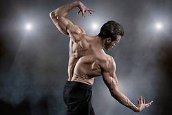 Muscular man flexing muscles while posing on stage