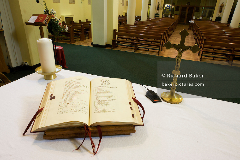 Open Bible and crucifix on altar in St. Lawrence's Catholic church in Feltham, London.