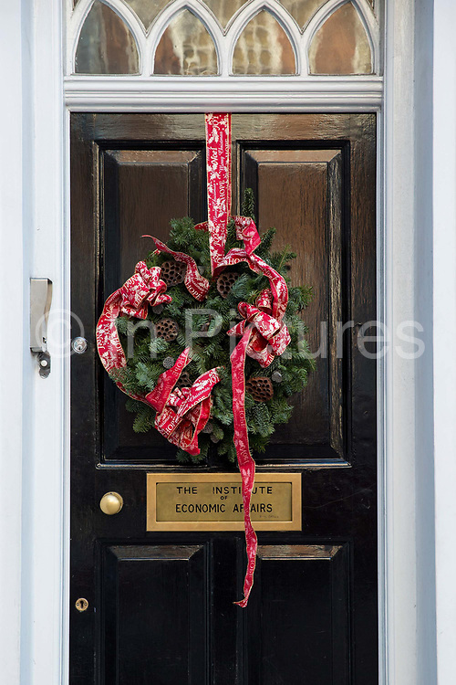 A large Christmas wreath hangs on the door of the Institute of Economic Affairs front door on the 13th December 2018 in Central London in the United Kingdom.