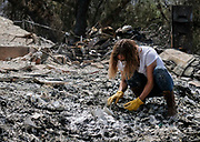 Lynn Dee Bollesen, daughter of home owner, surveys the charred debris left in a burned out home, Monday, Sept. 4, 2017, in the Sunland-Tujunga of Los Angeles, the United States, on Sept. 4, 2017. More than 1,000 firefighters work for a fourth day to put out a 7,000-acre brushfire that is 30 percent contained, as the last of the residents ordered to evacuate the record-setting blaze were expected to<br /> return to their homes authorities said. (Xinhua/Zhao Hanrong)(Photo by Ringo Chiu)<br /> <br /> Usage Notes: This content is intended for editorial use only. For other uses, additional clearances may be required.