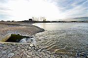 Nederland, Nijmegen, 10-12-2015 De nevengeul aan de overkant van de Waal bij Lent.  In de nieuwe dijk is een drempel gebouwd die stapsgewijs water doorlaat en bij hoogwater overloopt. Zicht op de inlaat, de drempel waar de geul begint. Grootste onderdeel van de vele werken van Rijkswaterstaat om bij hoogwater een betere waterafvoer in de rivier te hebben. Het is een omvangrijk project waarbij onder meer de pijlers van het spoorviaduct een bredere basis kregen omdat die straks in de loop van het water staan. Ook de n325 die vanaf de Waalbrug naar Arnhem loopt is over 400 meter opnieuw aangelegd omdat het talud vervangen wordt door een nieuwe brug met drie gracieuze pijlers. Het dorp veurlent komt op een kunstmatig eiland te liggen met twee bruggen als ontsluiting. Ruimte voor de rivier, water, waal.The Netherlands, Nijmegen. Measures taken by Nijmegen to give the river Waal, Rhine, more space to flow during highwater and to prevent the risk of flooding. Room for the river. Reducing the level, waterlevel. Large project to create a new paralel gully, an extra flow of water, so the river can drain more water during highwater. Due to climate change and expected rise, increase of the sealevel, the Dutch continue to protect their land from the water. Foto: Flip Franssen/HH