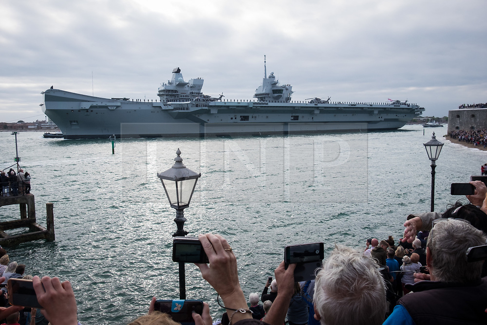 © Licensed to London News Pictures. 18/08/2018. Portsmouth, UK.  Crowds gathered to watch the Royal Navy's flagship, HMS Queen Elizabeth, sailing out of Portsmouth Naval Base this evening, 18th August 2018.  The 65,000 tonne aircraft carrier has set sail for an 11-week trip to perform trials with the F-35B aircraft off the coast of the United States.  Photo credit: Rob Arnold/LNP