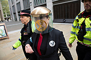 Climate change activist from the Extinction Rebellion group who has glued herself to colleagues at the entrance to the London Stock Exchange in the heart of the City of London financial district in protest that the government is not doing enough to avoid catastrophic climate change and to demand the government take radical action to save the planet is arrested by police, on 25th April 2019 in London, England, United Kingdom. Extinction Rebellion is a climate change group started in 2018 and has gained a huge following of people committed to peaceful protests.