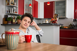 Young man sitting with a cup in his hands at the kitchen table, Munich, Bavaria, Germany