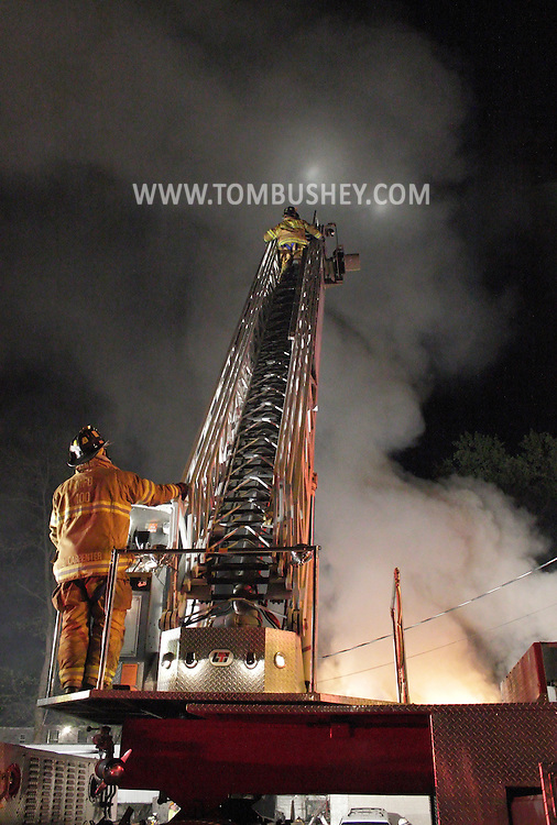 Middletown, New York - A firefighter climbs a ladder at the scene of a fire at The Engine Shop on North Street in Middletown late on the night of Friday, April 20, 2012.