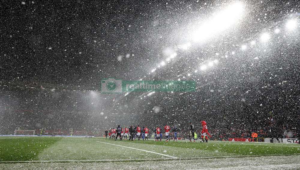 Both teams walk out into a snow storm before the Emirates FA Cup, quarter final match at Old Trafford, Manchester