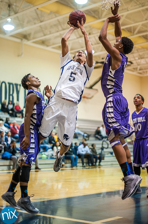 Hickory Ridge's Nick Hough (5) goes up for a shot against Cox Mill's TJ Jones (5) and Jonathan Earl (4) Tuesday night at Hickory Ridge High School. Cox Mill won the game 68-65.