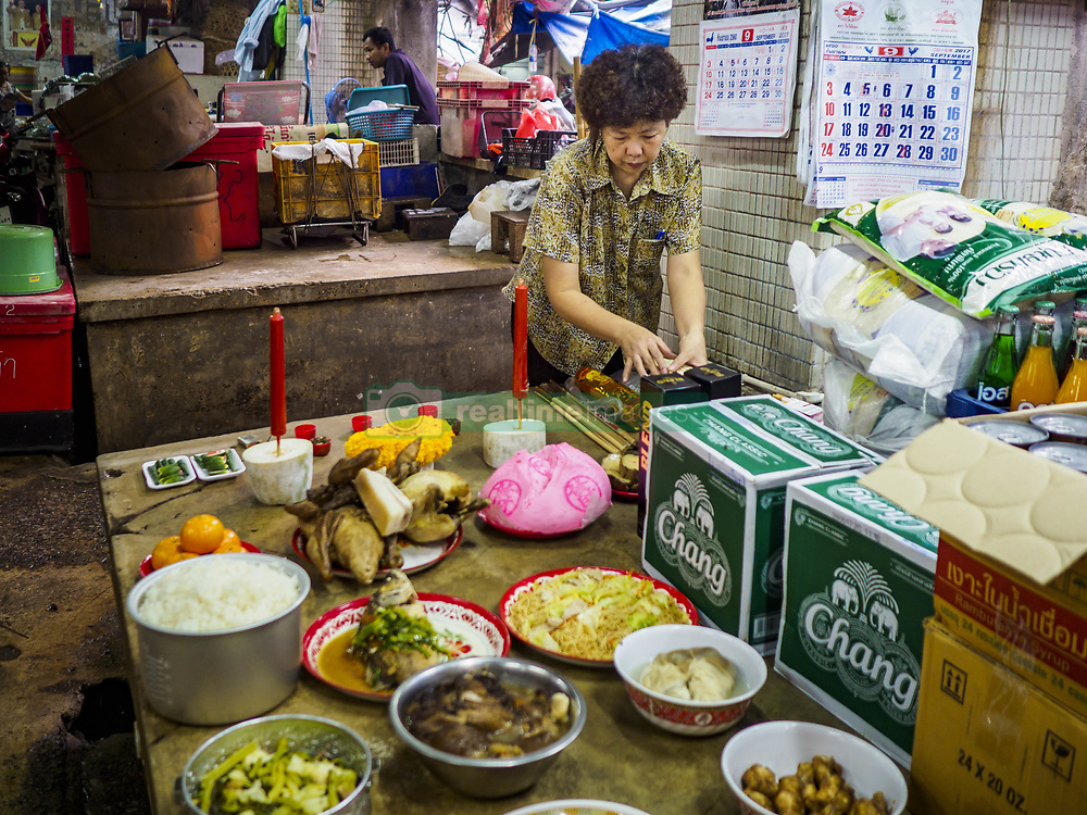 September 5, 2017 - Bangkok, Bangkok, Thailand - A woman sets up her Hungry Ghost Day banquet in a market in Bangkok's Chinatown. The Ghost Festival is a Buddhist and Taoist holy day celebrated on the 15th day of the 7th lunar month. In Thailand, it's celebrated in Thai-Chinese communities in Bangkok, Phuket and Chiang Mai.  On that day ghosts and spirits, including those of the deceased ancestors, come out from the lower realm to visit the living. Families prepare elaborate banquets for the spirits and burn ''ghost money'' for the spirits to use in the other realm. It is a day for venerating dead relatives. (Credit Image: © Jack Kurtz via ZUMA Wire)