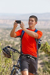 young bicyclist stopping to take a photograph with his iPhone outdoors in The Southwest near Santa Fe, NM