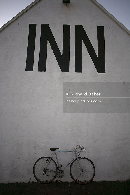 Leaning against the side wall of the eighteenth-century Stein Inn in the tiny Loch-side hamlet of Stein, Waternish, on the Isle of Skye, Scotland, a road-racing bicycle stands beneath a prominent three-letter sign saying 'Inn'. The image is in shadow and therefore monotone, with little colour except for the faint blue that is seen above from a fading sky. The wall is painted white and the word in block capitals is in black. The image is clean and simple without confusing elements or messages. The Inn itself is the oldest on Skye and is one of renowned travel writer's Alastair Sawday's special places to stay and which boasts 99 Malt Whiskies behind the counter.