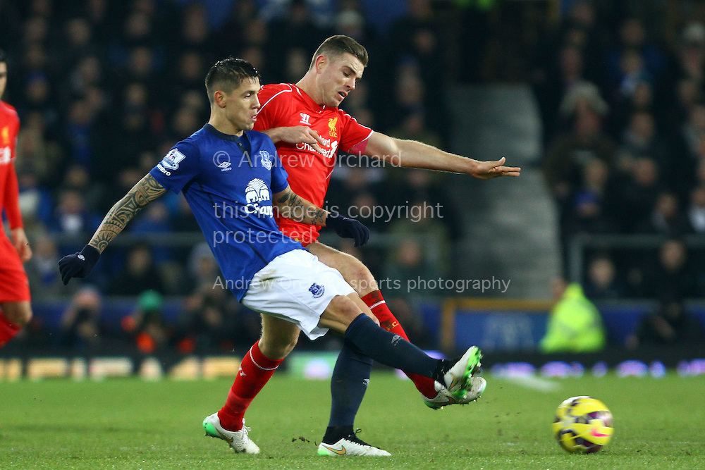Muhamed Besic of Everton passes under pressure from Jordan Henderson of Liverpool. Barclays Premier league match, Everton v Liverpool at Goodison Park in Liverpool, Merseyside on Saturday 7th February 2015<br /> pic by Chris Stading, Andrew Orchard sports photography.
