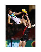 Chad Wingard get horizontal and Michael Hibberd of the Bombers at Marvel Stadium in Melbourne, Australia.