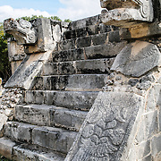Stone stairs leading to the top of a ceremonial platform, with carved jaguar heads guarding either side, at Chichen Itza Archological Zone, Yucatan, Mexico.
