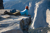 Young woman looking over 1000 ft cliff in Yosemite National Park, Ca.