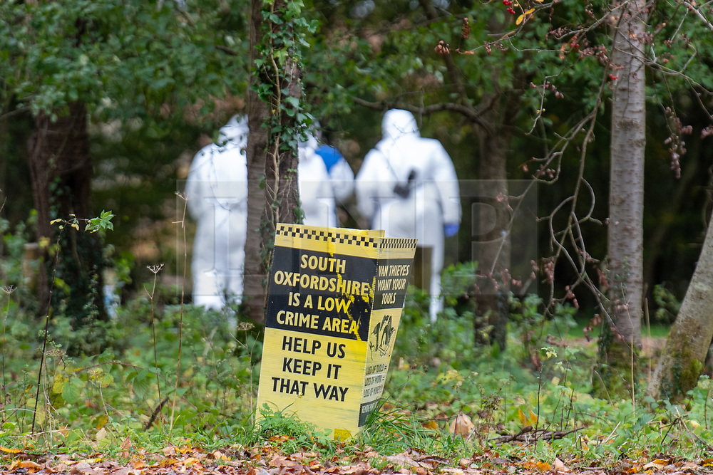 © Licensed to London News Pictures. 24/10/2020. Watlington Hill, UK. A sign in a carpark reads 'South Oxfordshire is a low crime area' as forensic investigators make there way down a path at the Watlington Hill National Trust Estate. A murder investigation has been launched by Thames Valley Police after the body of a woman in her sixties was located in woodland in the Watlington Hill National Trust Estate at approximately 5:53pm on Friday 23/10/2020. Photo credit: Peter Manning/LNP