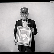 A portrait of Navajo Code Talker Peter MacDonald, Sr., holding an old U.S. Marine Corps photo of himself, July 10, 2019, outside his home in Tuba City, Arizona.