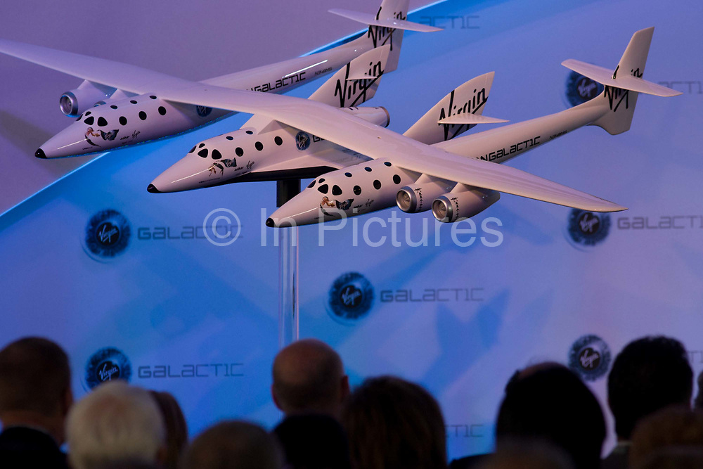 Audience silhouettes and scale model of Virgin Galactic's WhiteKnightTwo space vehicle with SpaceShipTwo in the middle at air show PR event. Designed by Robert Morgan & James Tighe, the Scaled Composites Model 348 White Knight Two (WK2) is a jet-powered cargo aircraft which will be used to launch the SpaceShipTwo spacecraft. It is being developed by Scaled Composites as the first stage of Tier 1b, a two-stage to suborbital-space manned launch system. WK2 is based on the successful mothership to SpaceShipOne, White Knight, which itself is based on Proteus.