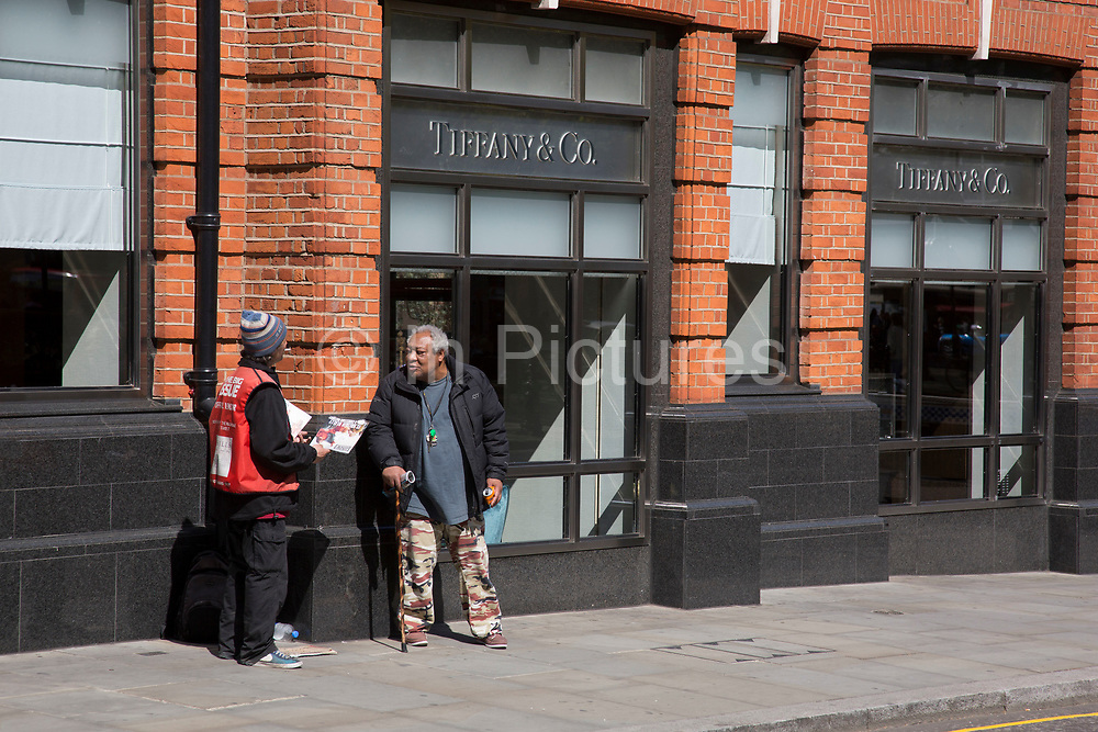 Big Issue seller talking to a friend while selling the magazine run by the homeless outside Tiffany and Co jewellery shop at Sloane Square in Chelsea. An example of rich and poor and the disparity of wealth that there is in the capital. In a selected few boroughs of West London, wealth has changed over the last couple of decades. Traditionally wealthy parts of town, have developed into new affluent playgrounds of the super rich. With influxes of foreign money in particular from the Middle-East. The UK capital is home to more multimillionaires than any other city in the world according to recent figures. Boasting a staggering 4,224 'ultra-high net worth' residents - people with a net worth of more than $30million, or £19.2million.. London, England, UK.