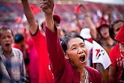 01 JULY 2011 - BANGKOK, THAILAND:   An 80 year old woman cheers for Pheua Thai parliamentary candidates during a Pheua Thai rally in Bangkok Friday. Thailand's divisive election campaign drew to a close Friday in Bangkok. Most of the parties had large rallies in an effort to sway last minute undecided voters. Pheua Thai, the party of ousted Prime Minister Thaksin Shinawatra held a massive rally in Rajamakala Stadium (also called Ramkamhaeng Stadium) to close out their campaign. A monsoon thunderstorm didn't keep people away from the event. Most Thai public opinion polls show Pheua Thai with a healthy lead over their arch rivals (and incumbent party in power) the Democrats. Thaksin's youngest sister, Yingluck Shinawatra, is running for Prime Minister under the Pheua Thai banner. If elected, she will be Thailand's first female Prime Minister.   PHOTO BY JACK KURTZ