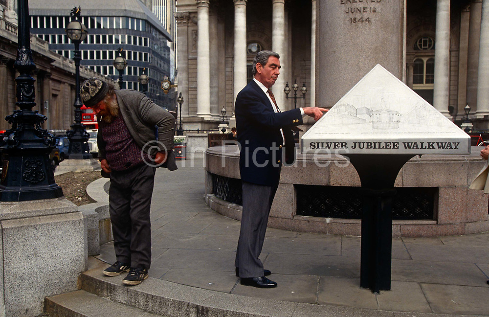 A poverty-stricken homeless man looks down at the pavement while a smartly-dressed professional puts a finger on his location on a steel map (and his own position in life) - a scene of wealth and prosperity and the downtrodden in society. They are both in a place known as Bank Triangle in what is called the Square Mile, London's oldest district of banking and finance businesses.