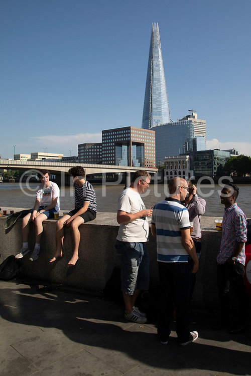 People hanging out having a drink outside a riverside pub opposite the Shard on the River Thames in London, England, United Kingdom.