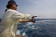 Offshore fly fishing angler palming spool to manage line drag.
