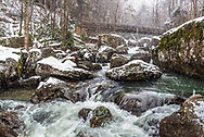 A snowy, wintery scene envelops the crisp blue waters flowing around the massive boulders that define the length of Wolf Creek in the New River Gorge of West Virginia.