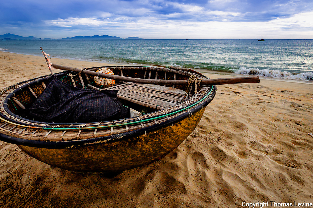 A round basket fishing boat used in Vietnam for fishing and travel tours. This one is beached for the day after being out at sea at night.