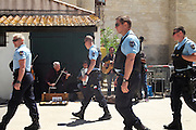 """A Romanian gypsy play near the church. French police patrol the seaside town of Saintes Maries de la Mer during the pilgrimage. With rising of the french 'Front National', which the Mayor belongs too, and racism and prejudice the gypsies feel less and less welcome these days to their own festival<br /><br />""""Le Pelerinage des Gitans""""; the French gypsy pilgrimage of Saintes Maries de la Mer, Camargue, France<br /><br />Sainte Sara is an uncannonized saint, who legend says looked after the Christian Saints Marie Jacobe and Marie Salome, cousins of Mary Magdalene, who arrived, it is said, on the shores of the Camargue in a rudderless boat. Saint Sara is the patron saint of gypsies who come from far and wide to see her. There are even paintings of Sara as 'Kali' the black saint in Eastern Europe. Sara may have been the priestess of 'Ra' the sun-god or even servant girl to the Christian saints. No-one really knows.<br /><br />For a few weeks of the year, Roma, Gitan and Manouche gypsies come from all over Europe in May, camping in caravans around Saintes Maries de la Mer. It is a festive time where they play music, dance, party and christen their children. They all go to see Saint Sara in the crypt, kissing or touching her forehead. Many put robes on her shoulders, making her fat for the procession. In the main Gypsy procession of the 24th May, Saint Sara is allowed to leave her crypt, beneath the church, and is carried from the church to the shores of the mediterranean and back again. One day a year she is free from her prison. Hundred's of years ago the Gypsies used not even to be allowed into the church, only into the crypt like Sara...<br /><br />Roma gypsies still suffer oppressive prejudice and racism and are one of the ethnic groups the most persecuted and marginalised across Europe. The festival is one of the times where they celebrate with people of all races, their faith and traditions"""