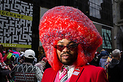 New York, NY - 21 April 2019. An African-American man in an oversized bright red Afro at the Easter Bonnet Parade and Festival on New York's Fifth Avenue.