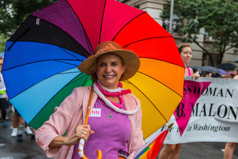 A woman with a rainbow umbrella wearing a tag in support of Christine Quinn's mayoral race  marches down Christopher Street.