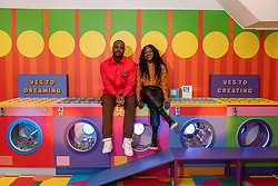 © Licensed to London News Pictures. 27/10/2021. LONDON, UK.  Award-winning artist and designer Yinka Ilori and Alero Akuya, VP of LEGO Global Brand development, as he unveils his 'Launderette of Dreams', a new installation where he has reimagined a community launderette in his signature colourful style. Made from over 200,000 LEGO bricks, the installation forms part of the LEGO Group's Rebuild the World campaign that celebrates children as masters of creative problem solving.  It can be found in Bethnal Green Rd, Shoreditch, 28 October to 6 November 2021..  Photo credit: Stephen Chung/LNP