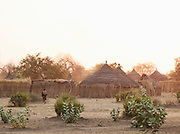 Person walking towards thatched huts at sunset in the village of Nyaro, of the Nuba tribe in Kordofan Region, Sudan