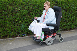Older woman wheelchair user coming back from shopping,