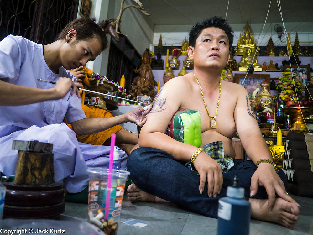 """22 MARCH 2013 - NAKHON CHAI SI, NAKHON PATHOM, THAILAND: A man gets a sacred Sak Yant tattoo at Wat Bang Phra. Wat Bang Phra is the best known """"Sak Yant"""" tattoo temple in Thailand. It's located in Nakhon Pathom province, about 40 miles from Bangkok. The tattoos are given with hollow stainless steel needles and are thought to possess magical powers of protection. The tattoos, which are given by Buddhist monks, are popular with soldiers, policeman and gangsters, people who generally live in harm's way. The tattoo must be activated to remain powerful and the annual Wai Khru Ceremony (tattoo festival) at the temple draws thousands of devotees who come to the temple to activate or renew the tattoos. People go into trance like states and then assume the personality of their tattoo, so people with tiger tattoos assume the personality of a tiger, people with monkey tattoos take on the personality of a monkey and so on. In recent years the tattoo festival has become popular with tourists who make the trip to Nakorn Pathom province to see a side of """"exotic"""" Thailand. The 2013 tattoo festival was on March 23.    PHOTO BY JACK KURTZ"""