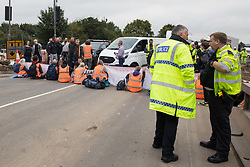 Enfield, UK. 15th September, 2021. Insulate Britain climate activists block a slip road from the M25 at Junction 25 as part of a campaign intended to push the UK government to make significant legislative change to start lowering emissions. The activists, who wrote to Prime Minister Boris Johnson on 13th August, are demanding that the government immediately promises both to fully fund and ensure the insulation of all social housing in Britain by 2025 and to produce within four months a legally binding national plan to fully fund and ensure the full low-energy and low-carbon whole-house retrofit, with no externalised costs, of all homes in Britain by 2030 as part of a just transition to full decarbonisation of all parts of society and the economy. Credit: Mark Kerrison